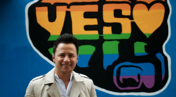 "Ryan Dolan poses for the camera in front of a ""Yes"" poster in Ireland, ahead of the May 22 referendum for marriage equality. (PHOTO: David Alexander; Star Observer)"